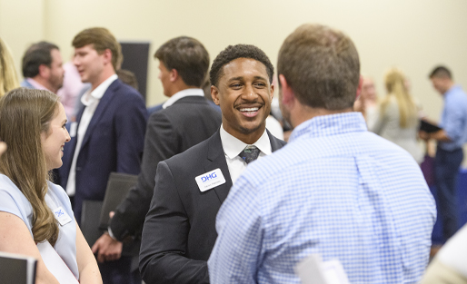 Darius Ramsey in a suit smiling engaged in conversation with a group at UM BAP Meet the Firms 2019